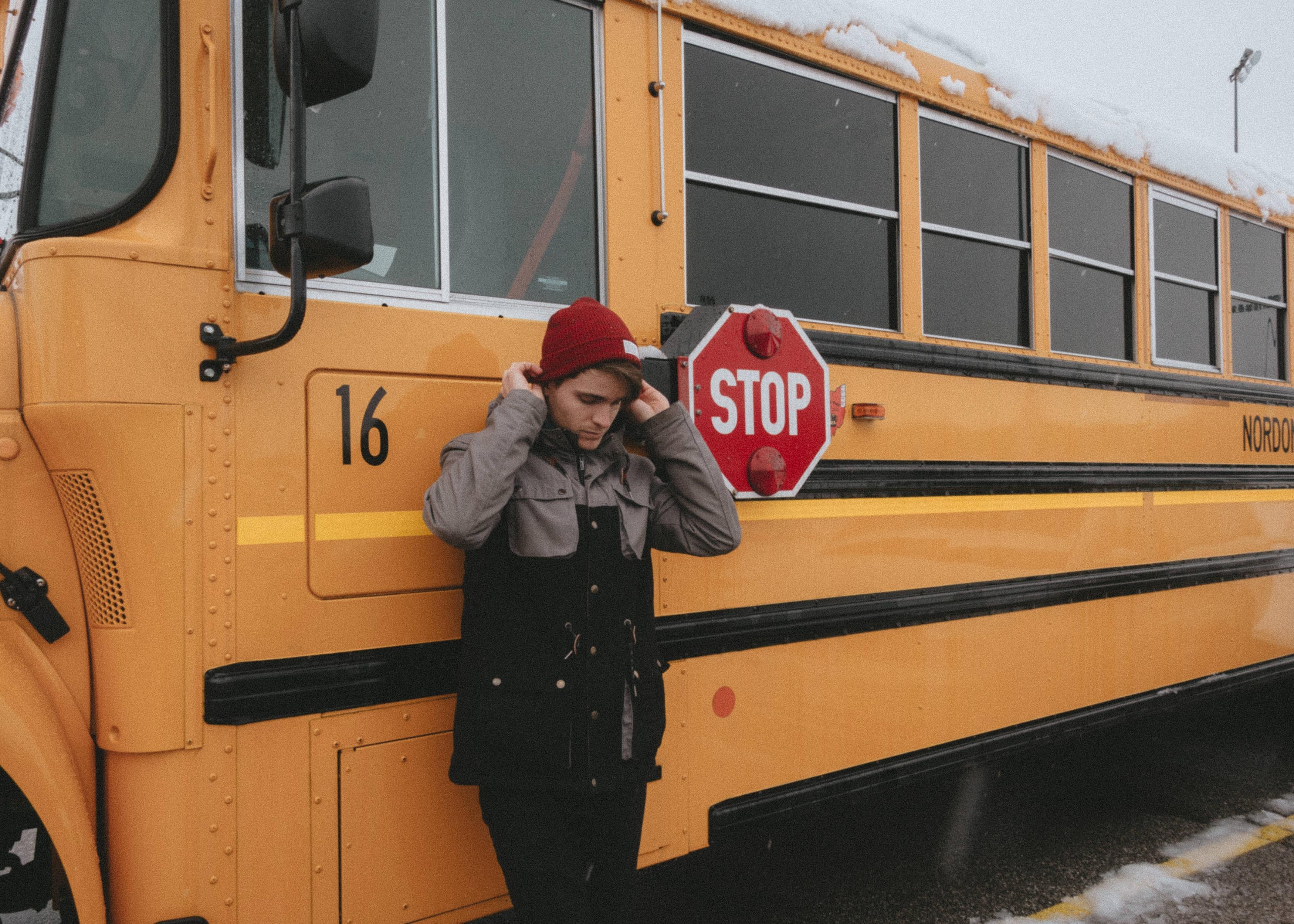 coa standing in front of school bus after winter break