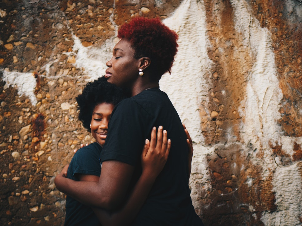 caring adult hugging a coa
