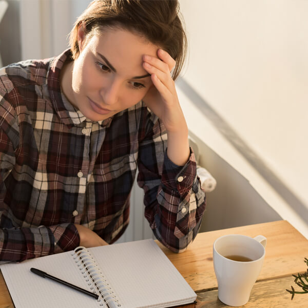 young woman struggling and looking deep in thought with empty notebook in front of her